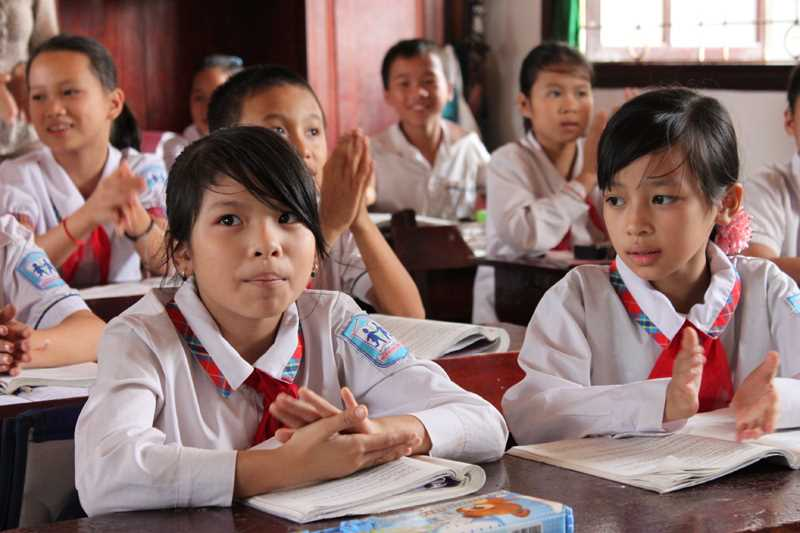 A photo of Vietnamese children in a classroom clapping their hands.